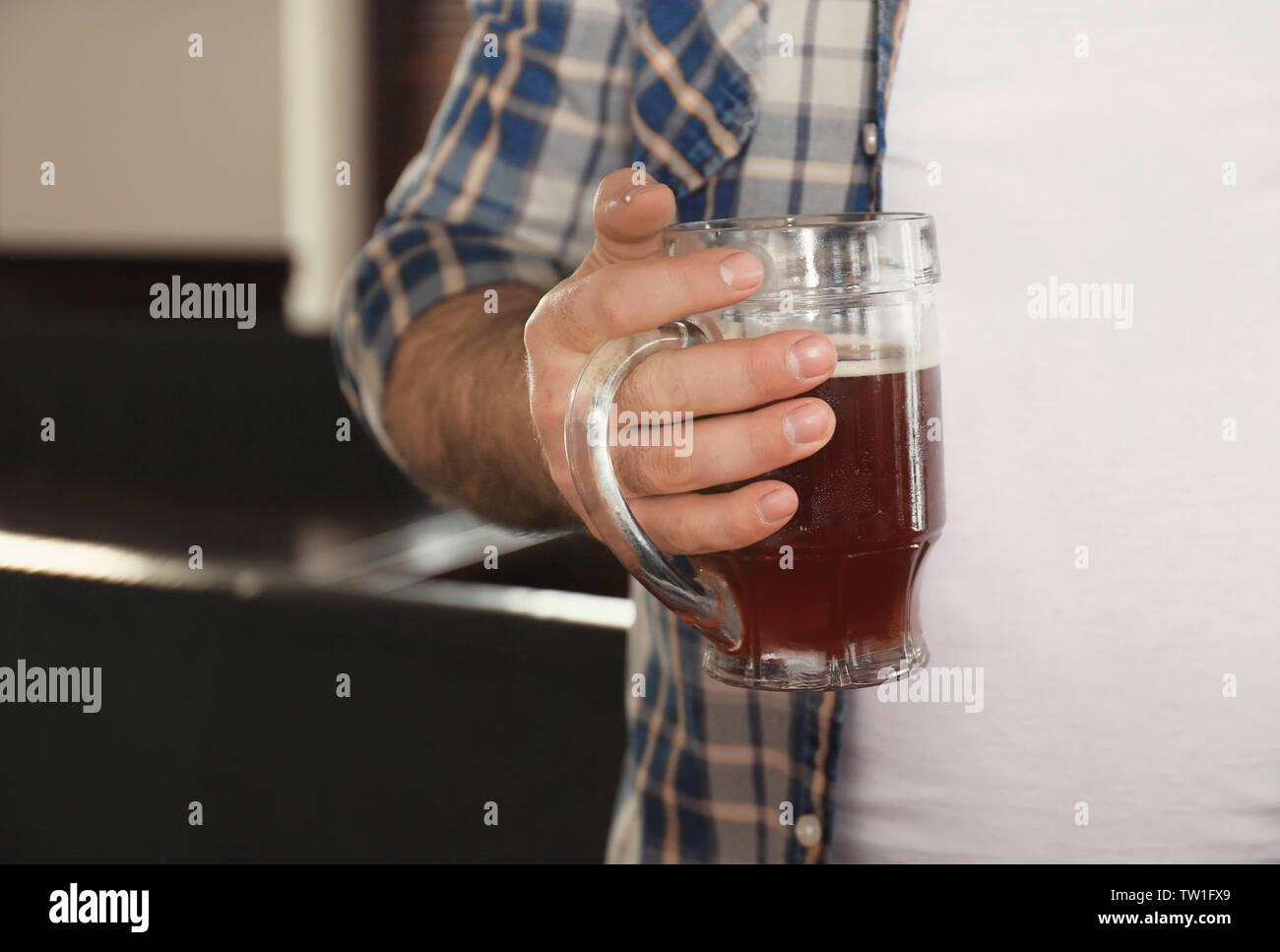 Mann hält ein Glas Bier in der Nähe seiner großen Bauch im Pub Stockbild
