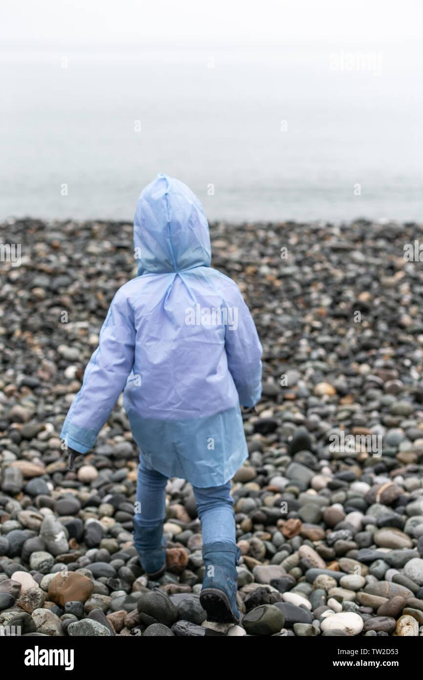 Zurück Sicht auf ein laufendes Kind zum Meer in einer Regenjacke und Gummistiefel. Selektive konzentrieren. Stockbild
