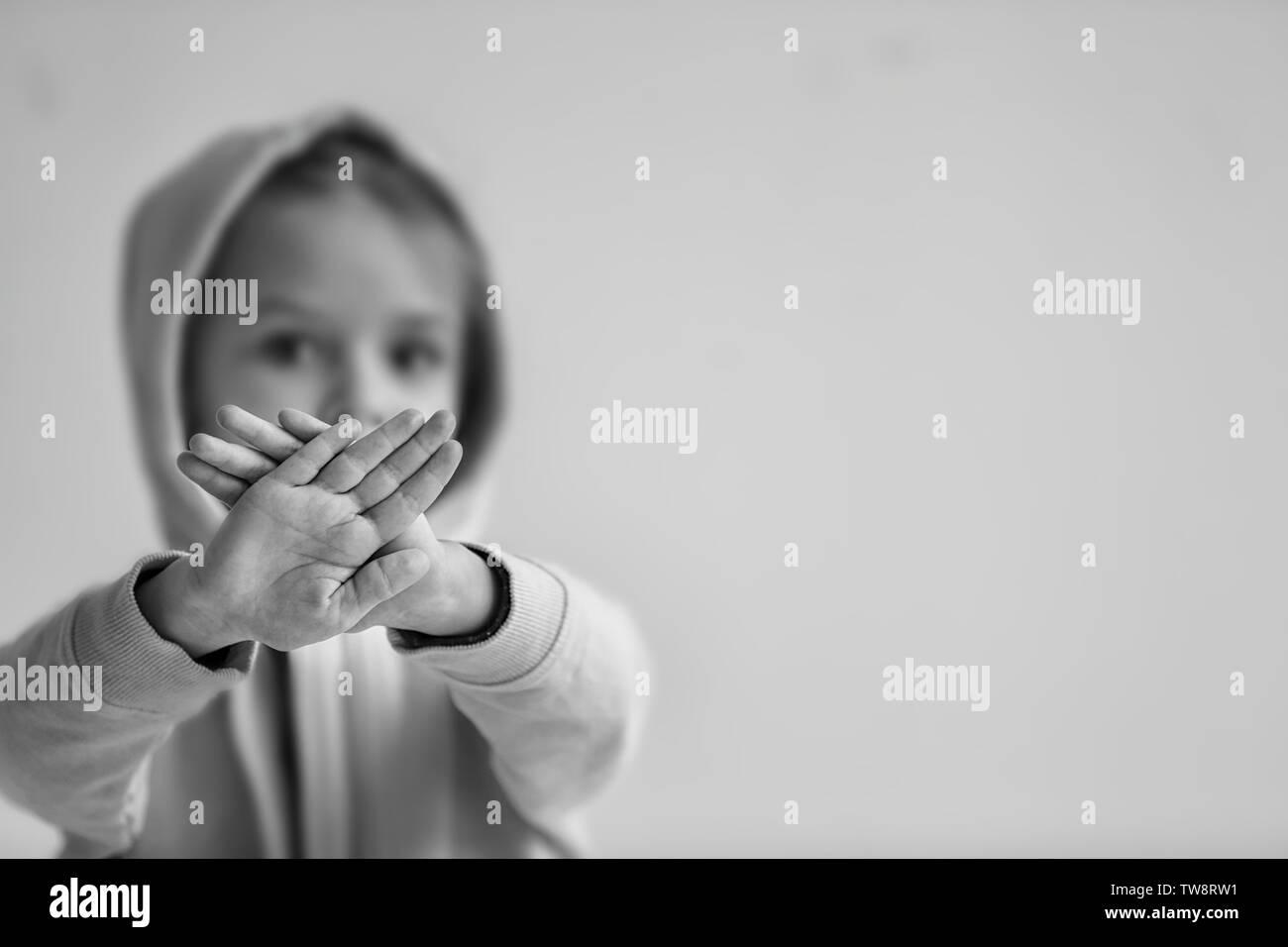 Trauriges kleines Mädchen, stop Geste auf grauem Hintergrund, schwarze und weiße Wirkung Stockbild