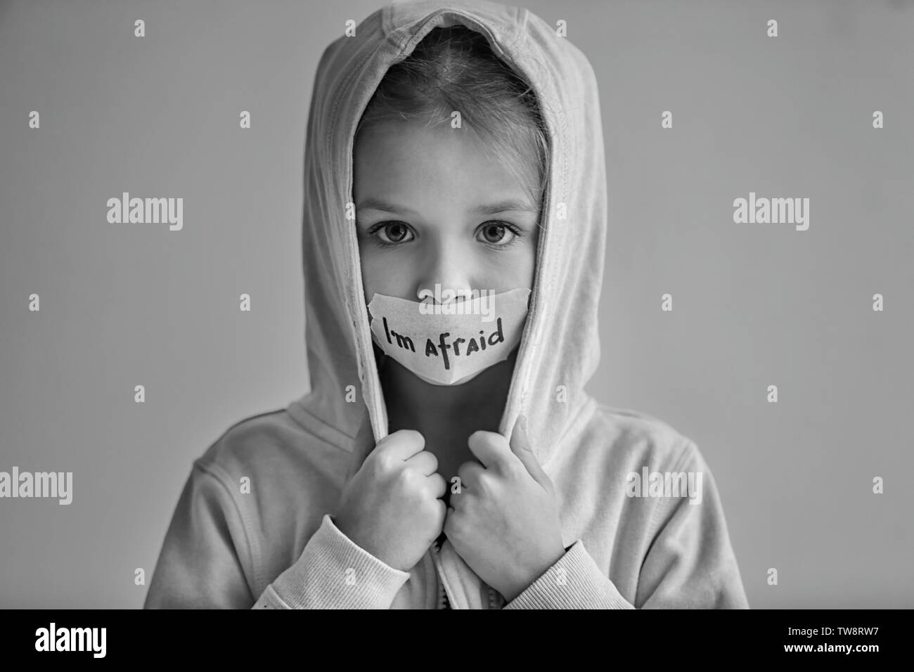 """Trauriges kleines Mädchen mit Getapten Mund und die Worte 'Ich bin auf grauem Hintergrund Angst"""", Schwarzweiß-Effekt Stockbild"""