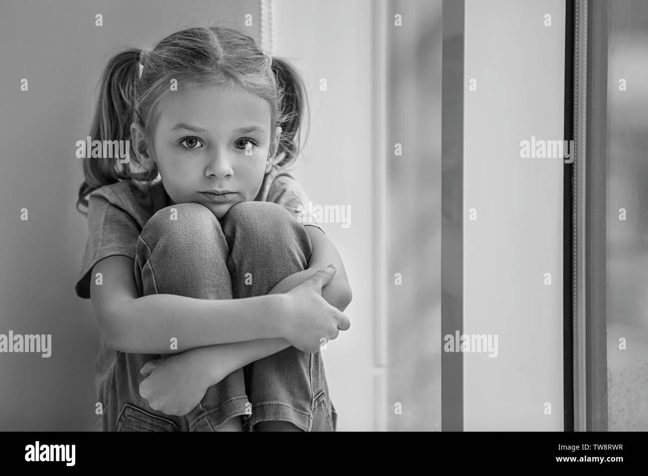 Trauriges kleines Mädchen saß auf der Fensterbank, Schwarzweiß-Effekt Stockbild