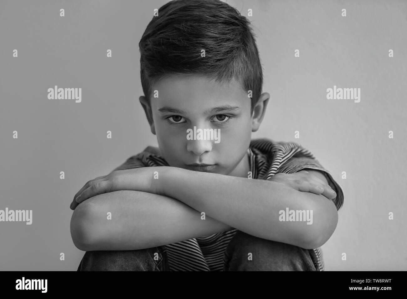 Traurige kleine Junge auf grauem Hintergrund, schwarze und weiße Wirkung Stockbild