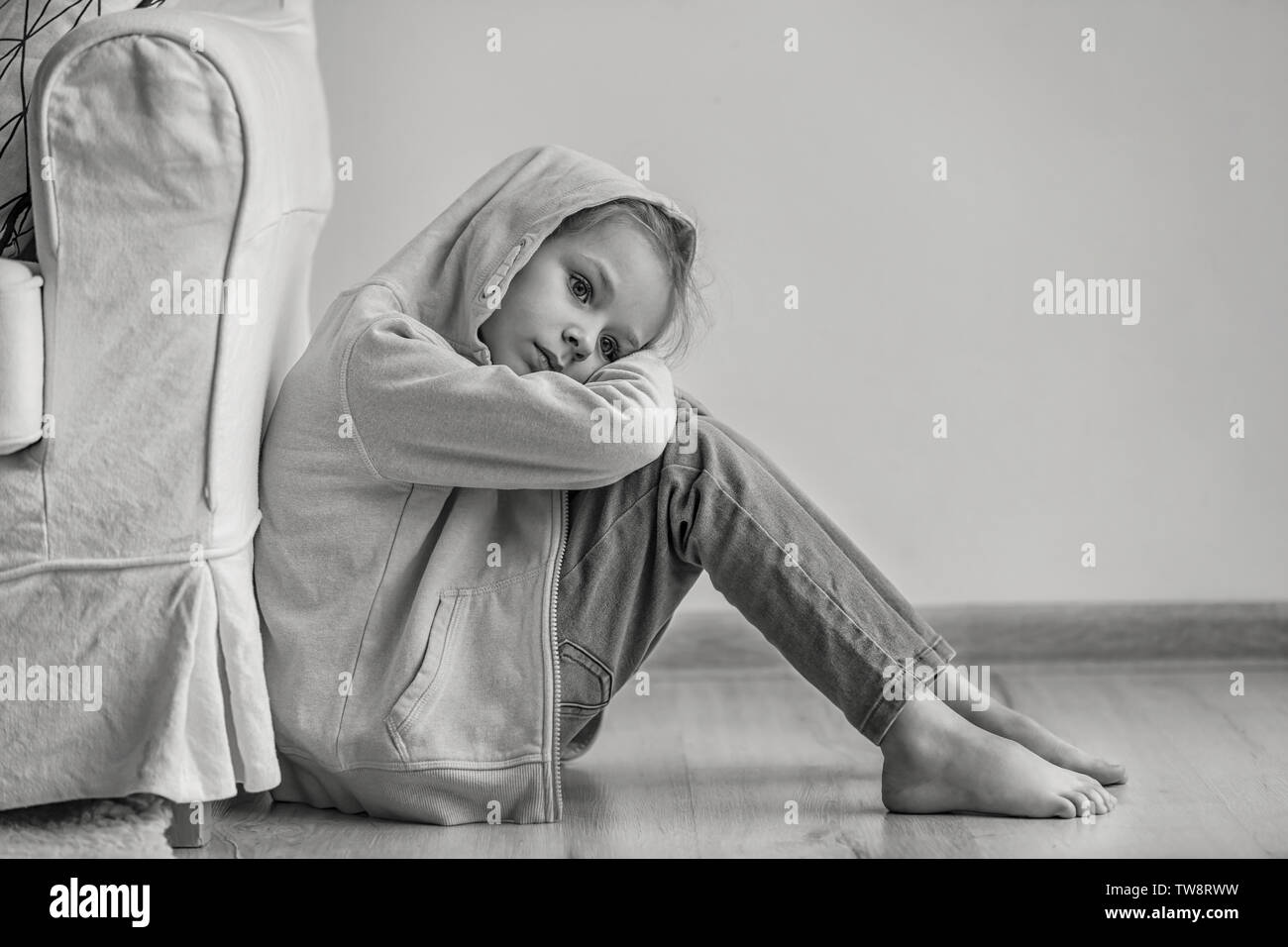 Trauriges kleines Mädchen sitzt auf dem Boden in Innenräumen, Schwarzweiß-Effekt Stockbild