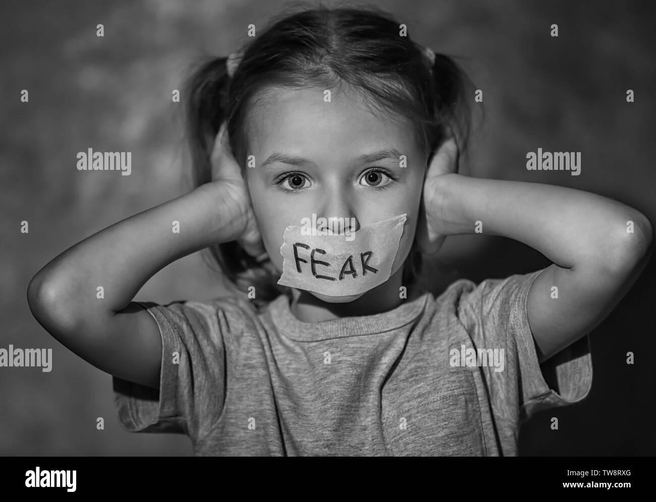 """Trauriges kleines Mädchen mit Getapten Mund und das Wort """"Angst"""" auf grauem Hintergrund, schwarze und weiße Wirkung Stockbild"""