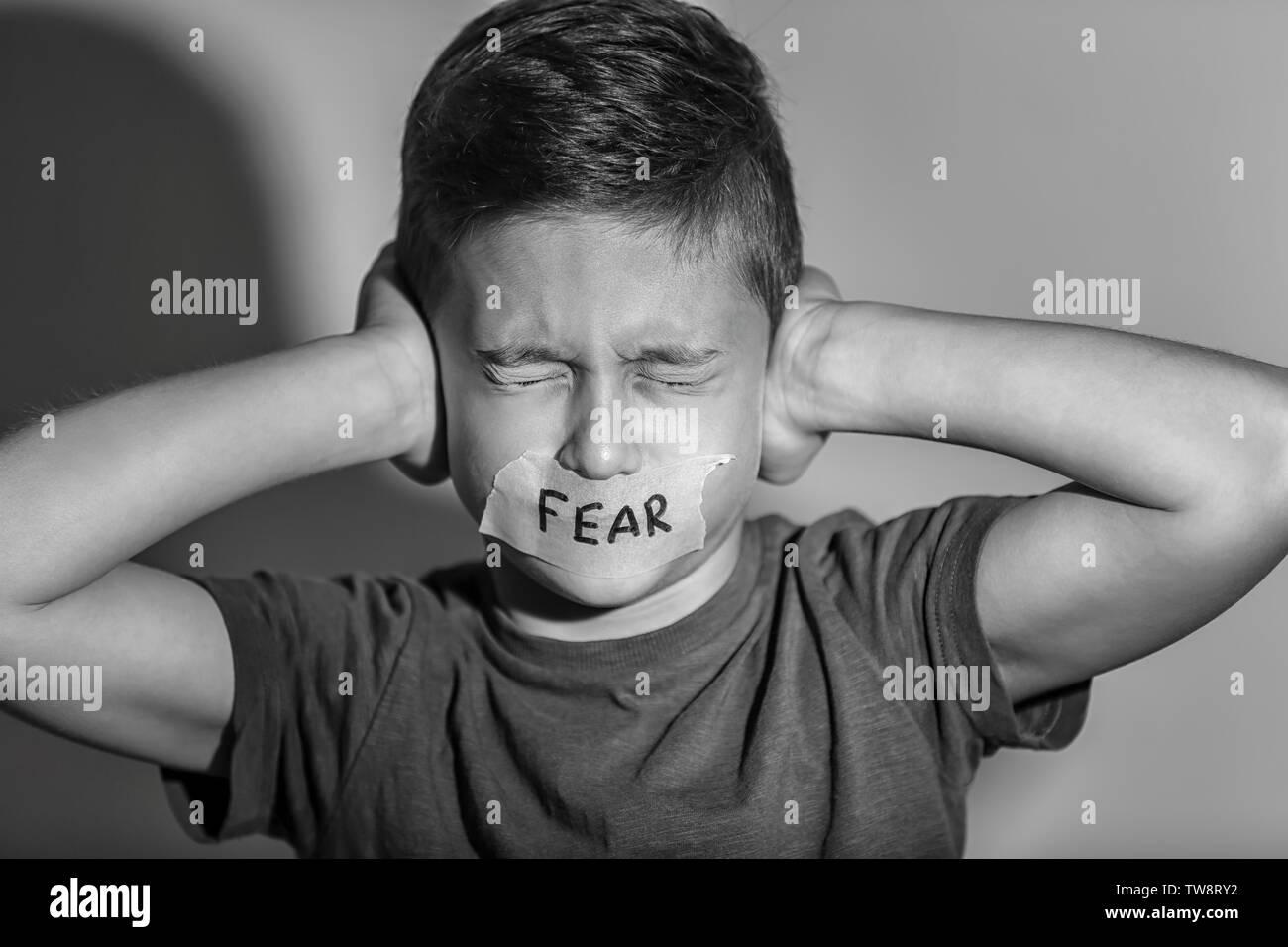 """Traurig kleiner Junge mit Getapten Mund und das Wort """"Angst"""" auf grauem Hintergrund, schwarze und weiße Wirkung Stockbild"""