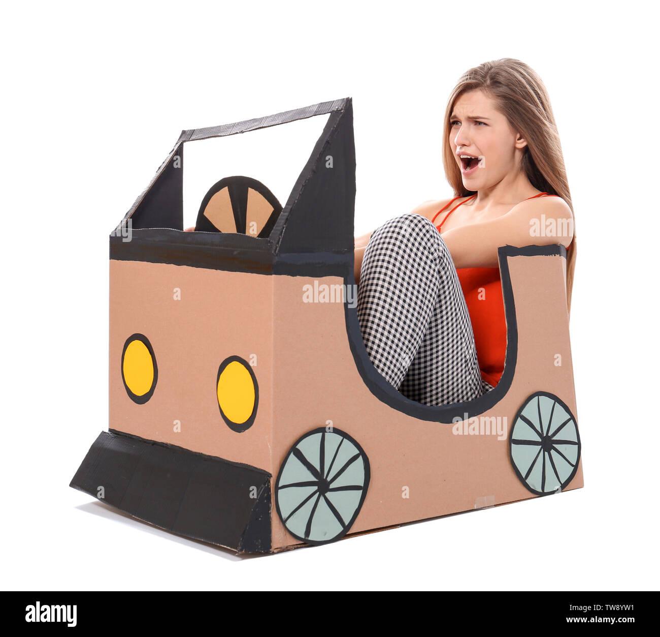 Junge Frau spielt mit Pappe Auto gegen den weißen Hintergrund. Konzept der Kauf neuer Autos Stockbild