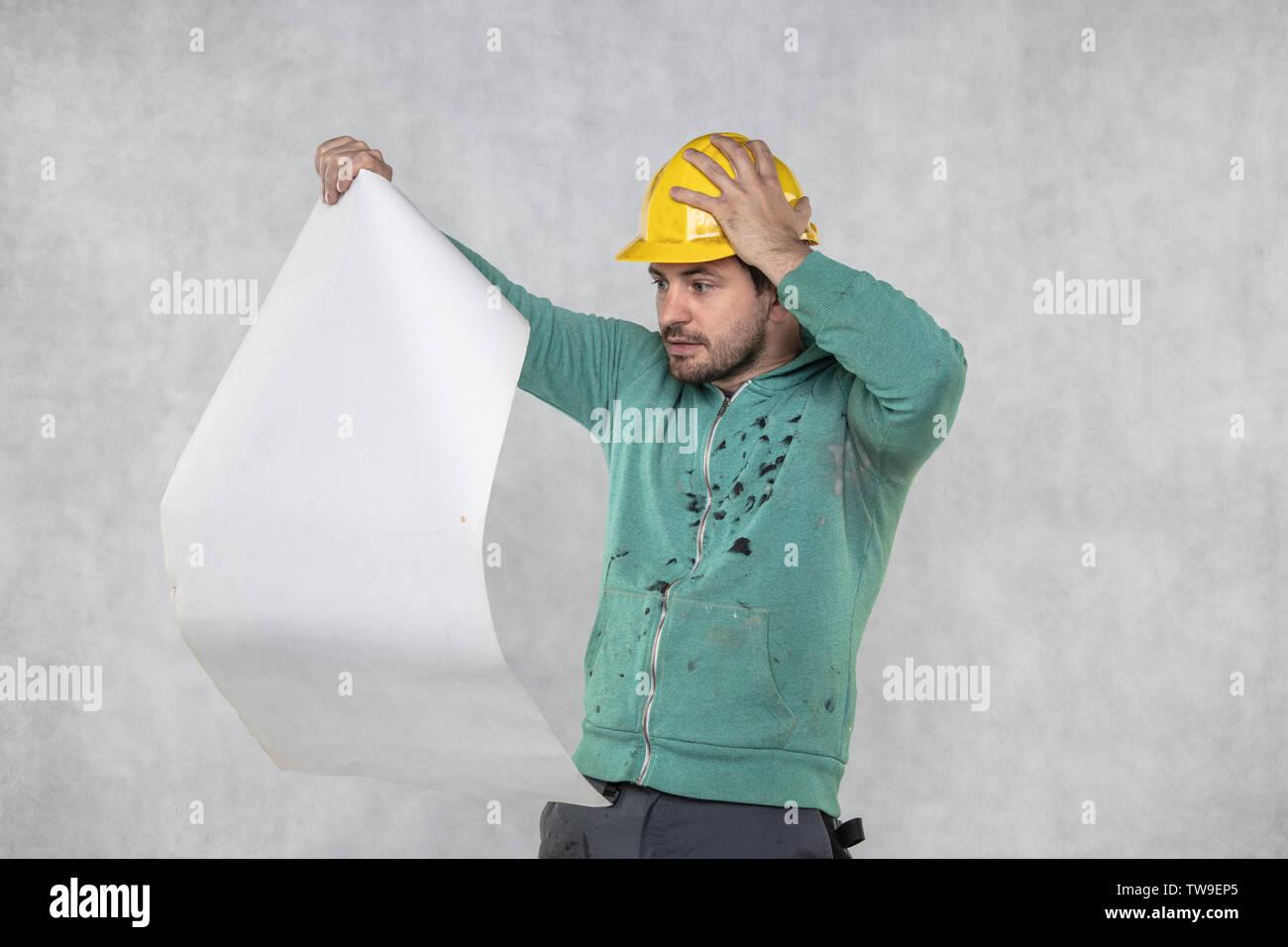 Erschrocken builder sieht Baupläne Stockbild