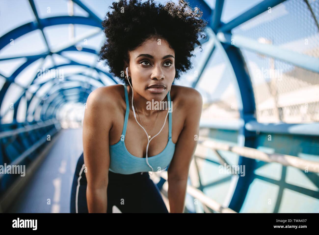 Junge Athletin über und Wegschauen gelehnt. Motiviert und konzentriert sportliche Frau vor einem laufen auf Gehweg Brücke. Stockfoto