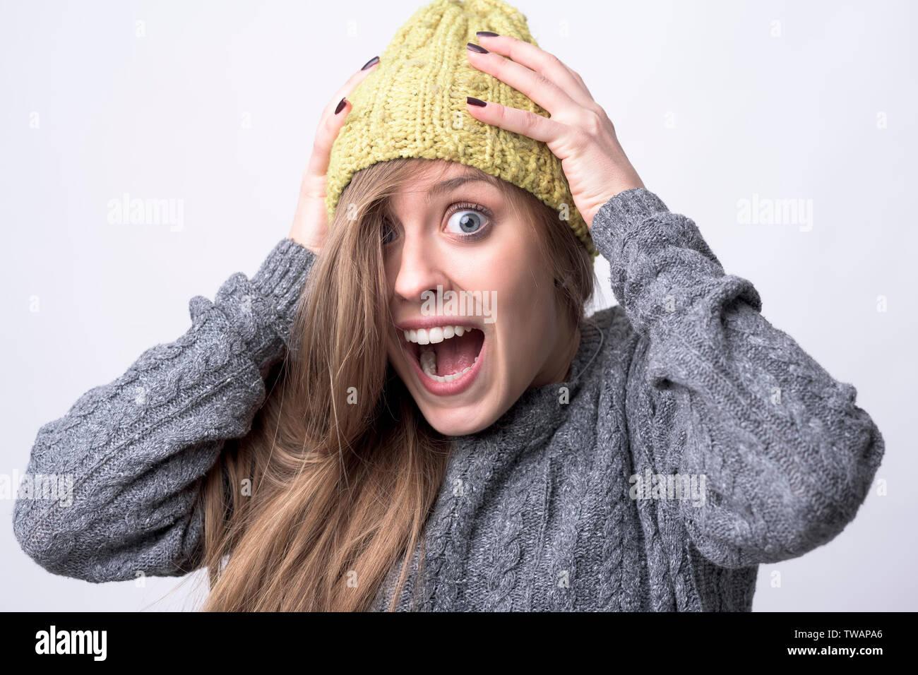 Close up Portrait von Ausdrucksstarken junge Frau schreien mit den Händen am Kopf auf hellgrauem Hintergrund. Stockbild