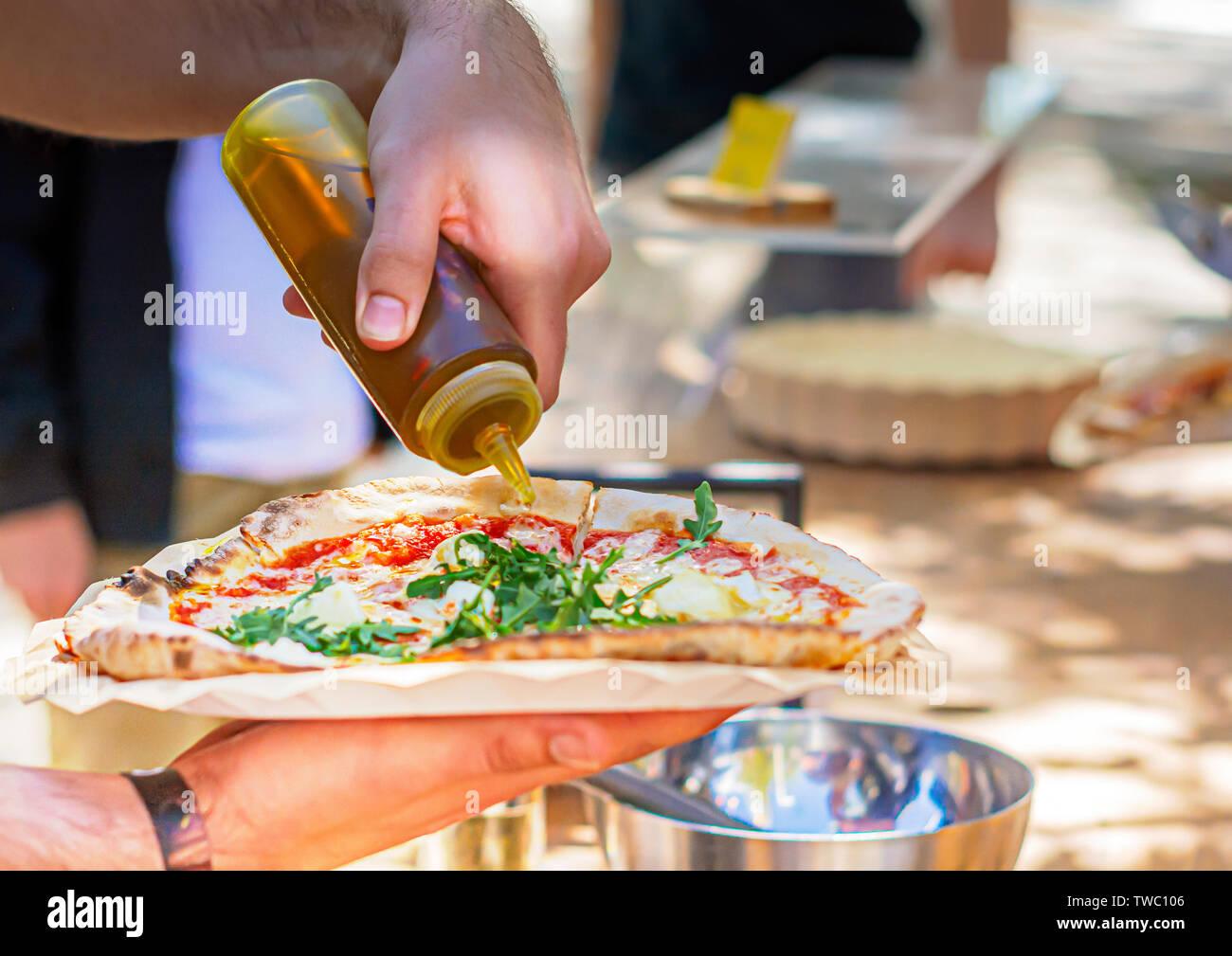 Ein männlicher gießen Olivenöl eine Pizza. Italienische ...