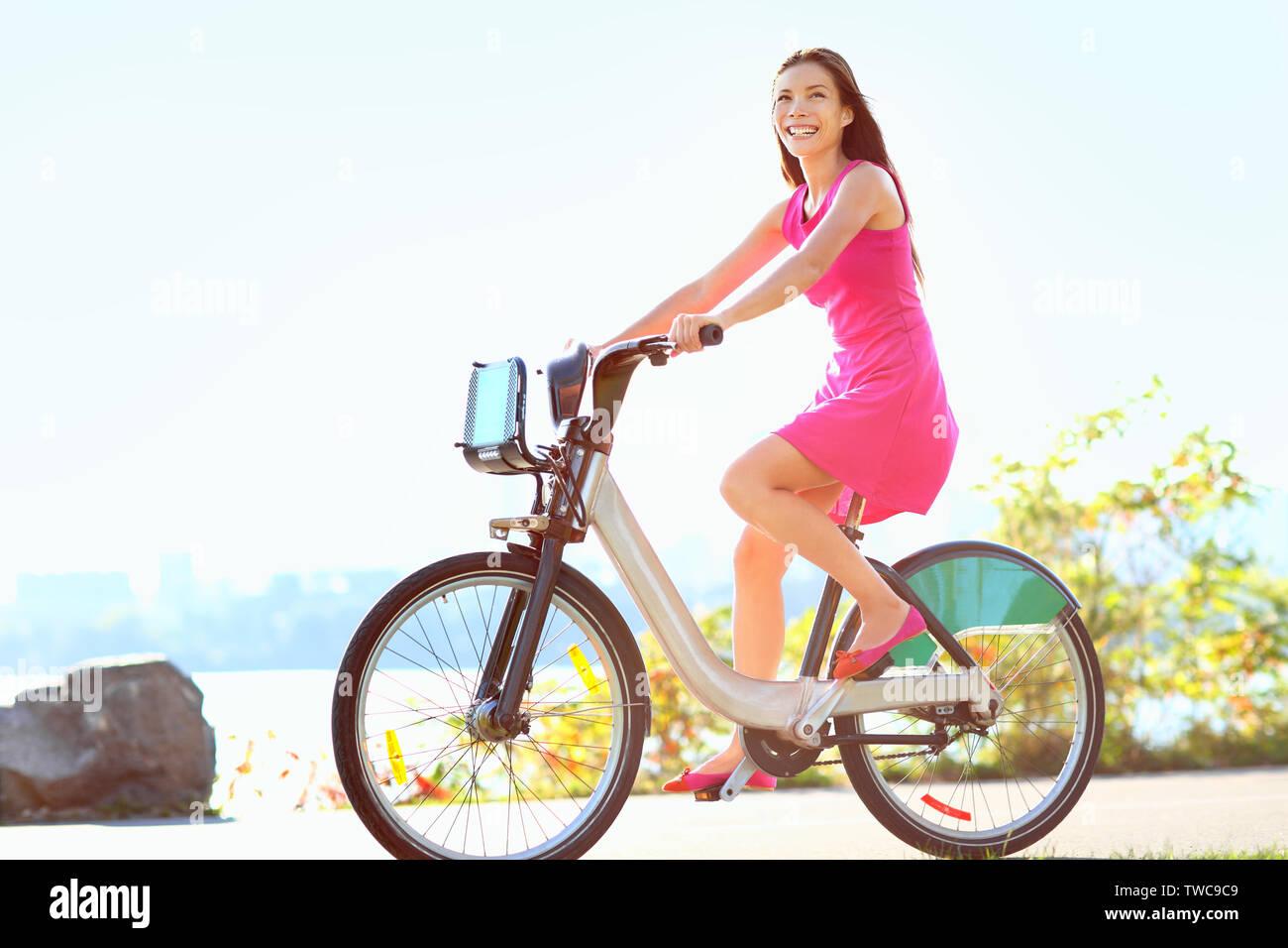 Mädchen Fahrrad fahren in der Stadt auf dem Fahrrad. Glückliche Frau auf Fahrrad Radfahren im Freien im Sommer ein Lächeln der Freude bei Aktivitäten im Freien. Gemischten rennen Kaukasischen asiatische Frau Modell. Stockfoto