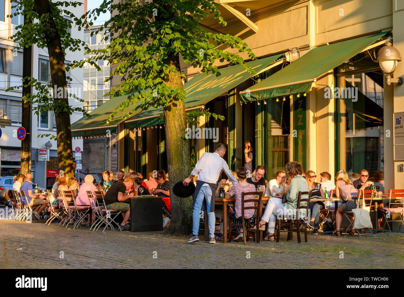 Berlin, Deutschland - 17. Juni 2019: Die Gäste Essen und Trinken in einem Restaurant im Zentrum von Berlin. In der voll besetzten Tische und Stühle stehen auf den Stockbild