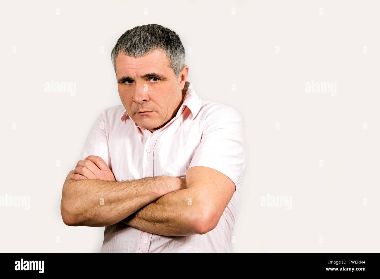 Ein Mann in einem hellen Hemd auf einem weißen Hintergrund. Gefühl von Traurigkeit und Enttäuschung, verärgert, beleidigt. Stockbild