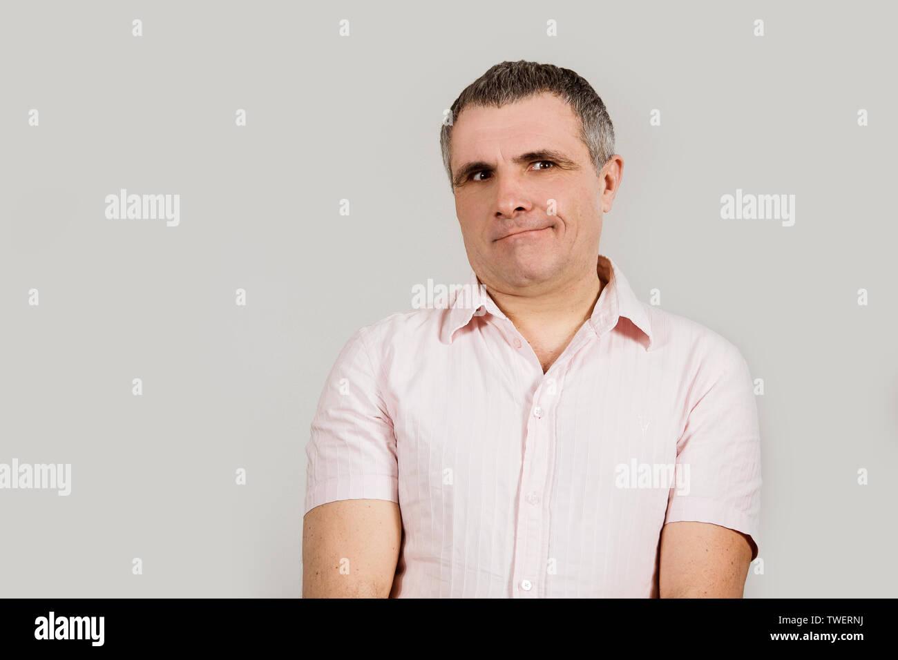 Ein Mann in einem hellen Hemd auf einem weißen Hintergrund. Ein Gefühl der Trauer, nicht verstehen und lassen Sie sich überraschen. Stockbild