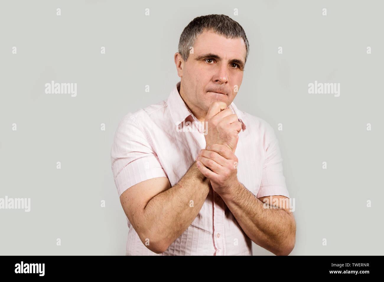 Ein Mann in einem hellen Hemd auf einem weißen Hintergrund. Gefühl von Unverständnis, Aggression, kämpfen will, das Böse, Kriminelle. Stockbild