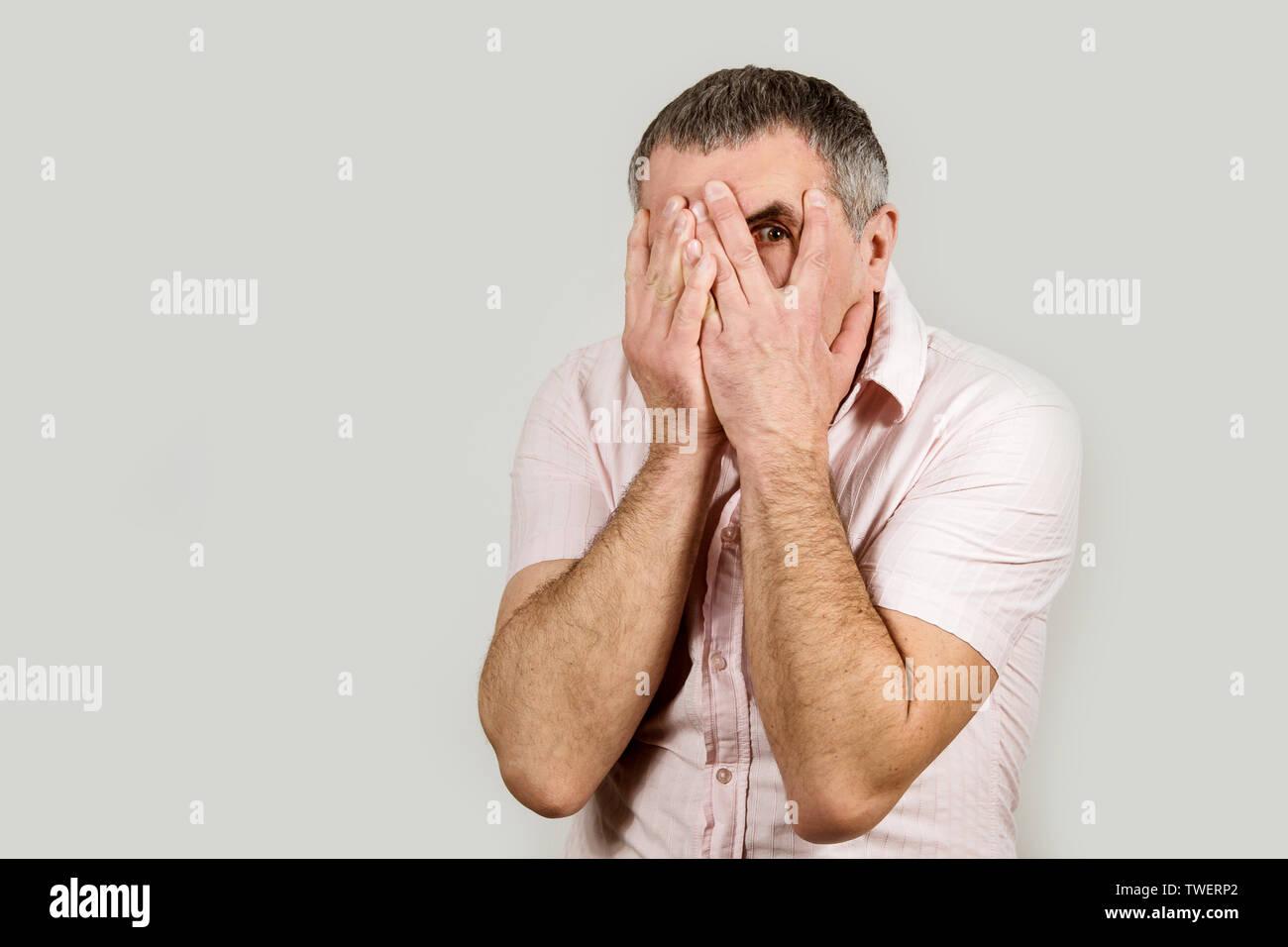 Ein Mann in einem hellen Hemd auf einem weißen Hintergrund. Gefühl von Traurigkeit und Frustration. Stockbild
