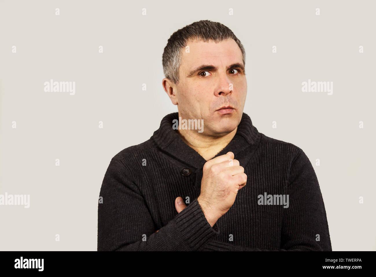 Ein Mann in einem dunklen pullover auf einem weißen Hintergrund. Emotionaler Mensch selbst aufgebracht. Stockbild