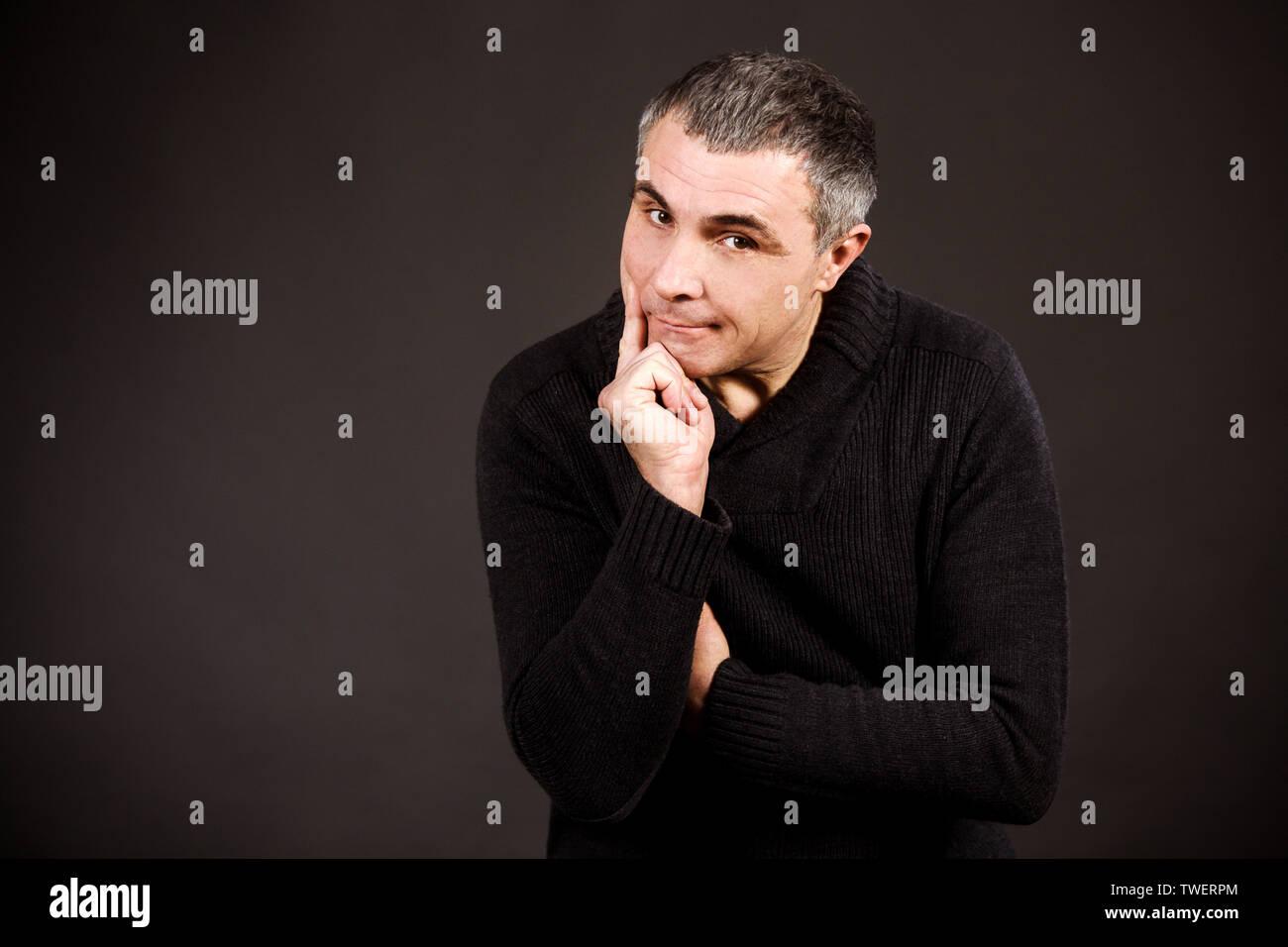 Ein Mann in einem dunklen pullover auf schwarzem Hintergrund. Emotionaler Mensch sich verärgert, er dachte und machte eine wichtige Entscheidung. Stockbild