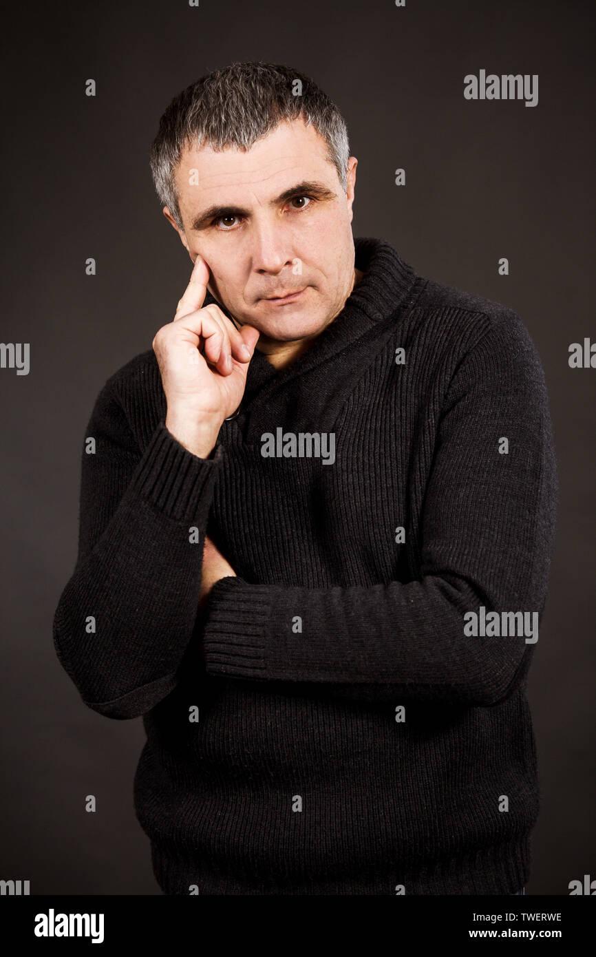Ein Mann in einem dunklen pullover auf schwarzem Hintergrund überlegt und entscheidet. Der Mann denkt über die Schwere und löst die emotionale Problem. Stockbild