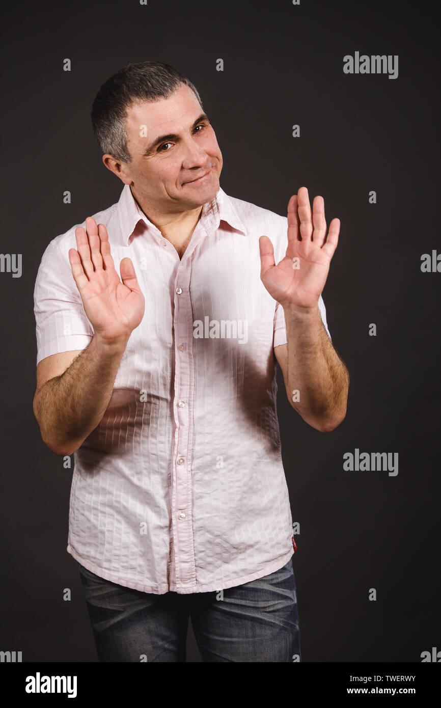 Ein Mann in einem hellen Hemd auf einem dunklen Hintergrund versucht, den Gesprächspartner zu beruhigen. Der Mann zeigt seine Hände, dass alles gut werden wird. Stockbild
