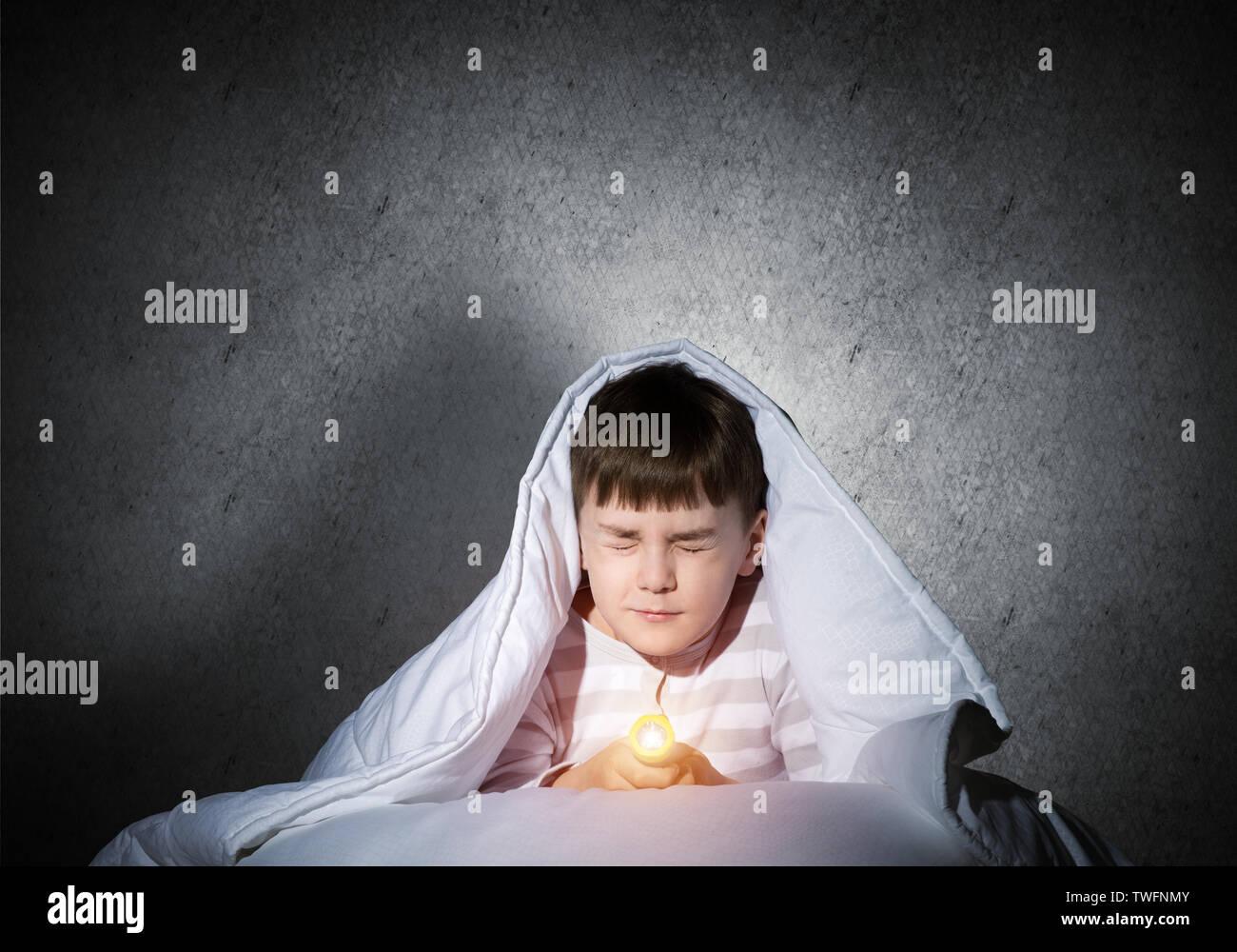 Verängstigten Kind mit der Taschenlampe unter der Bettdecke versteckt. Angst Kind mit geschlossenen Augen im Bett zu Hause liegen. Kleiner Junge kann nachts nicht schlafen. Portrait o Stockbild