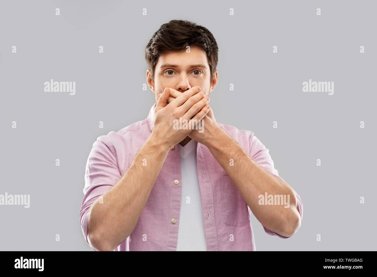 Junger Mann mit seinen Mund mit der Hand schockiert Stockbild