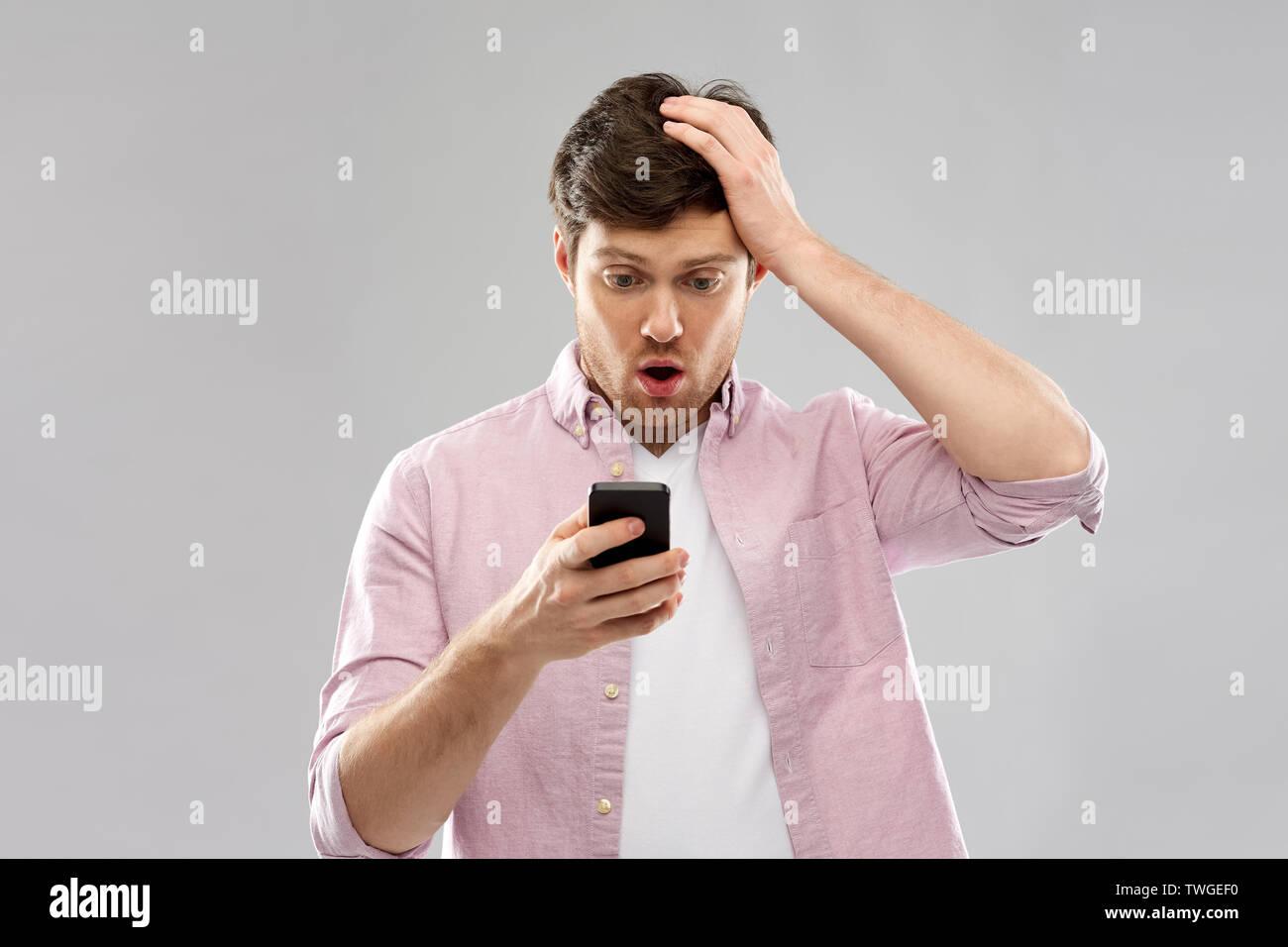 Peinlich junge Mann an Smartphone suchen Stockbild