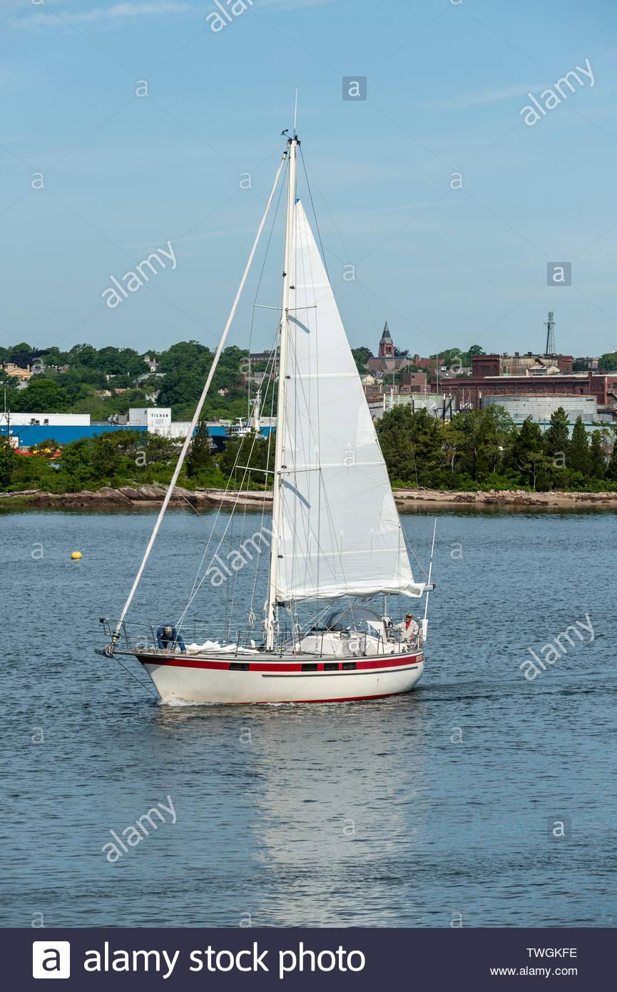 New Bedford, Massachusetts, USA - 15. Juni 2019: Crewman anschickt, Jib als Segelboot verlässt New Bedford mit Palmer Insel im Hintergrund Stockbild