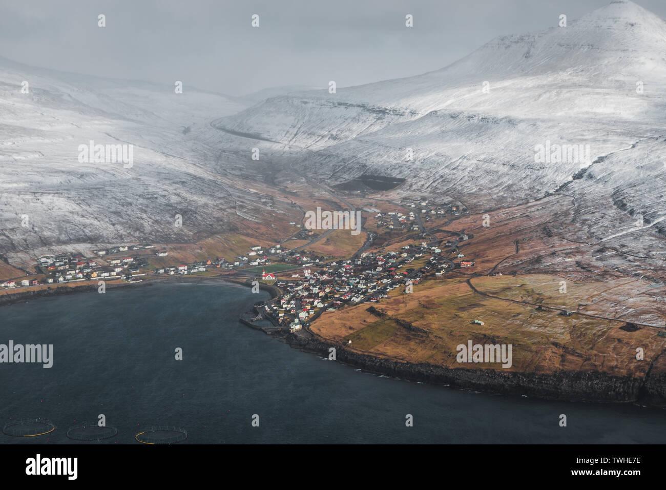 Luftaufnahme von einem färöischen Dorf in einer ruhigen Bucht umgeben von schneebedeckten Bergen wie von einem Hubschrauber im Frühjahr gesehen (Färöer Inseln) Stockfoto