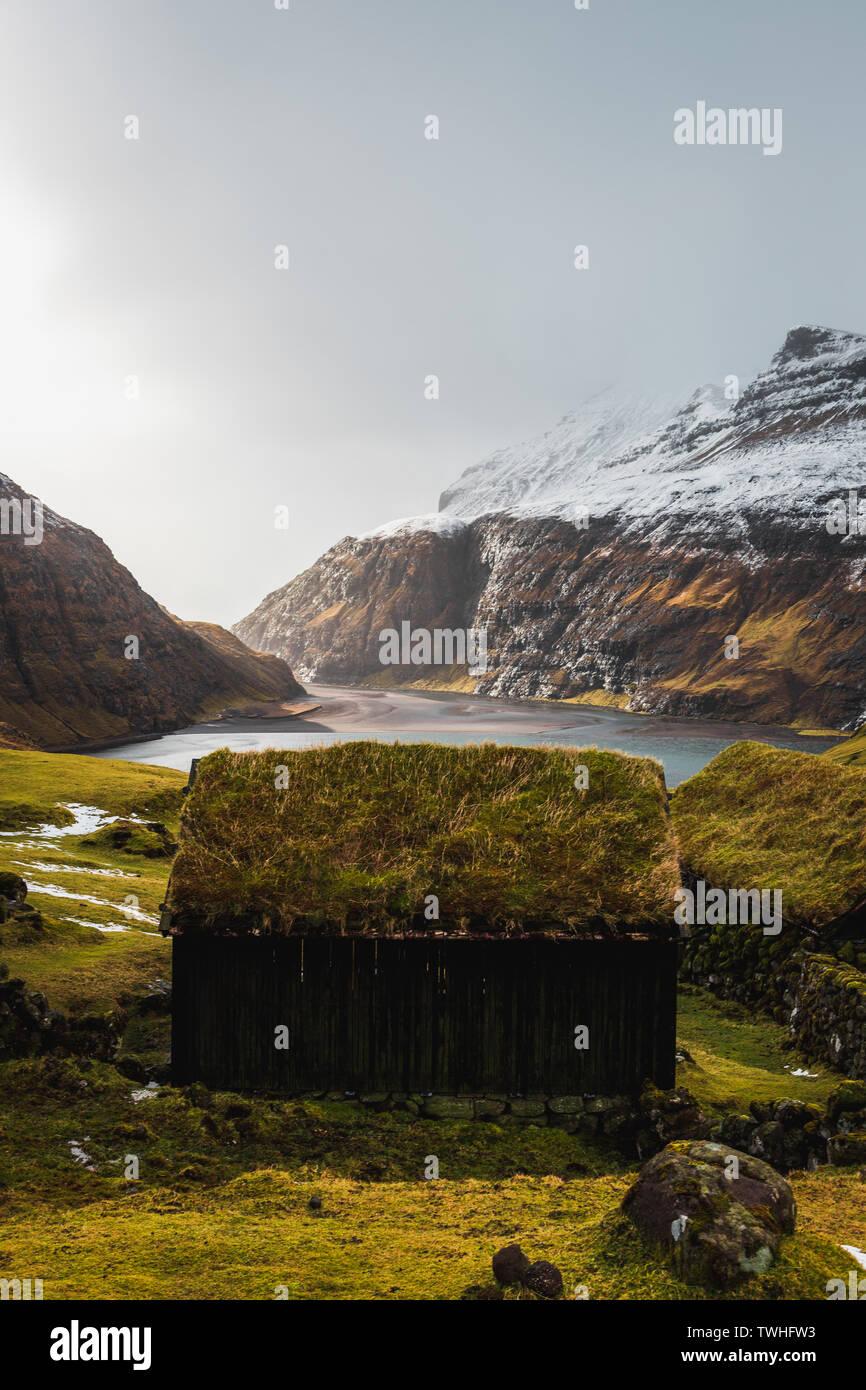 Typisch Färöischen, mit Gras bewachsene Kabinen in dem kleinen Dorf Saksun während der frühen Frühling mit schneebedeckten Bergen und tiefblauen Meer (Färöer Inseln) Stockfoto