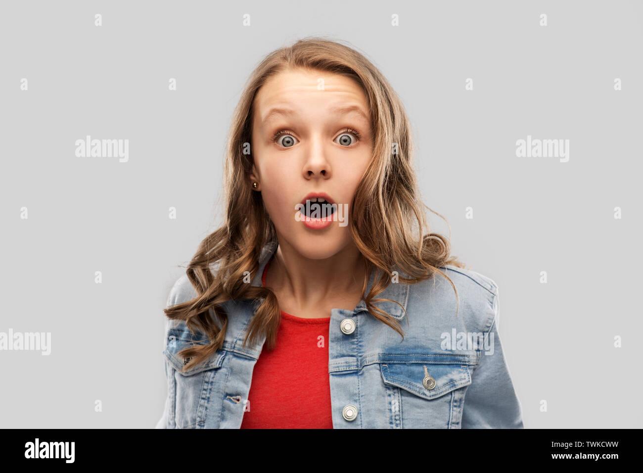 Überrascht oder junges Mädchen im roten T-Shirt schockiert Stockbild