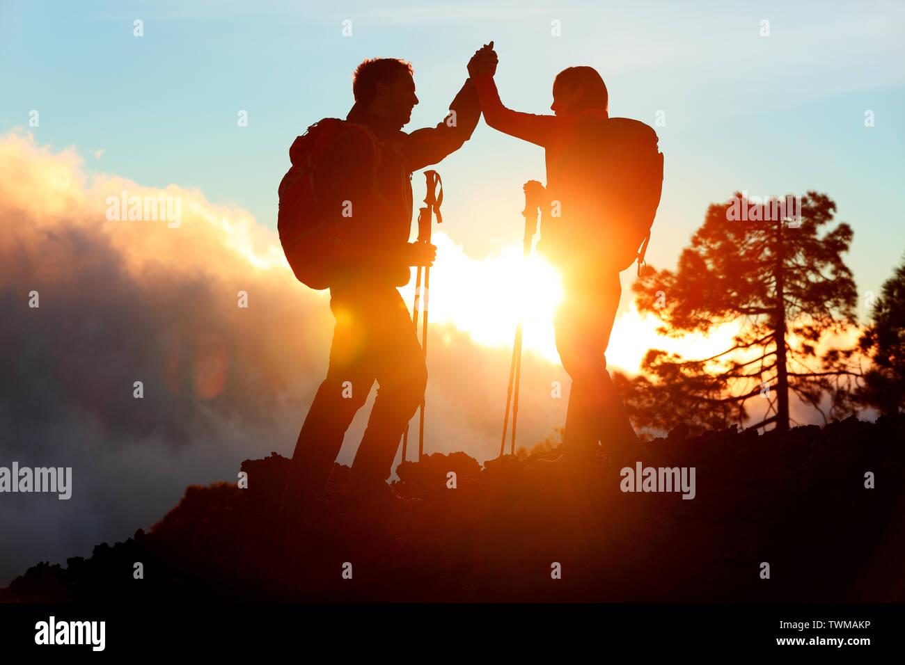 Wandern Menschen erreichen Gipfel top hoch fünf am Berg oben bei Sonnenuntergang. Happy Wanderer paar Silhouette. Erfolg, Leistung und Erfolg Menschen Stockfoto