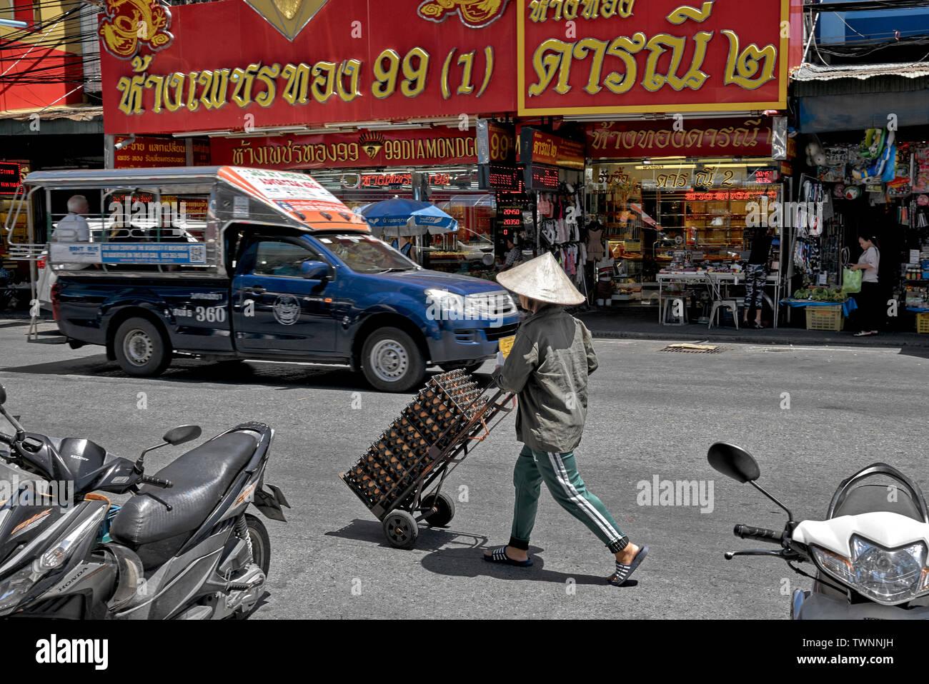 Frau mit einem traditionellen vietnamesischen konische Hut und den Transport von Eiern entlang einer Thailand Straße Stockbild