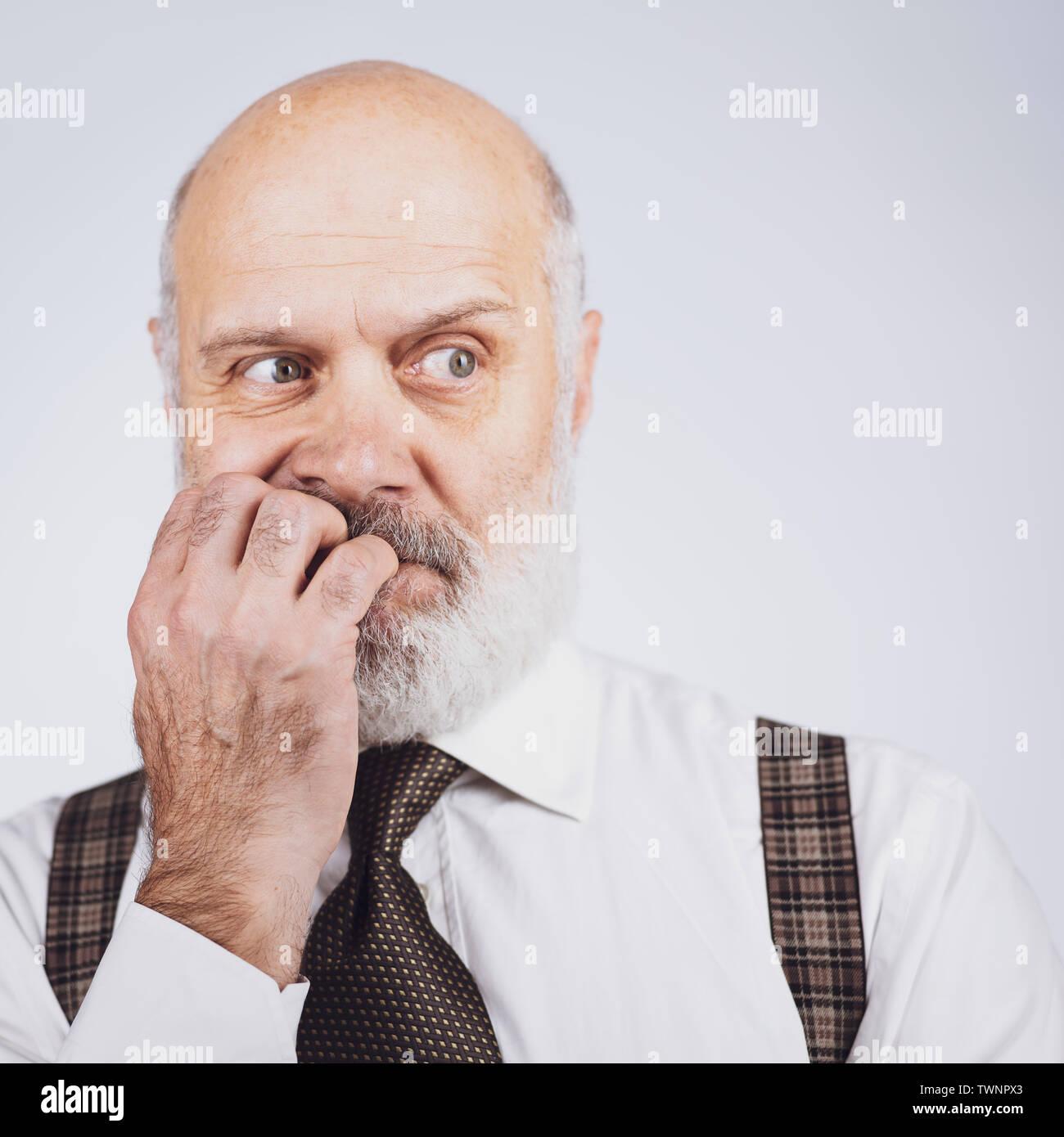 Nervös, ängstlich Senior Business Mann beißt seine Nägel, er ist erschrocken und besorgt Stockbild