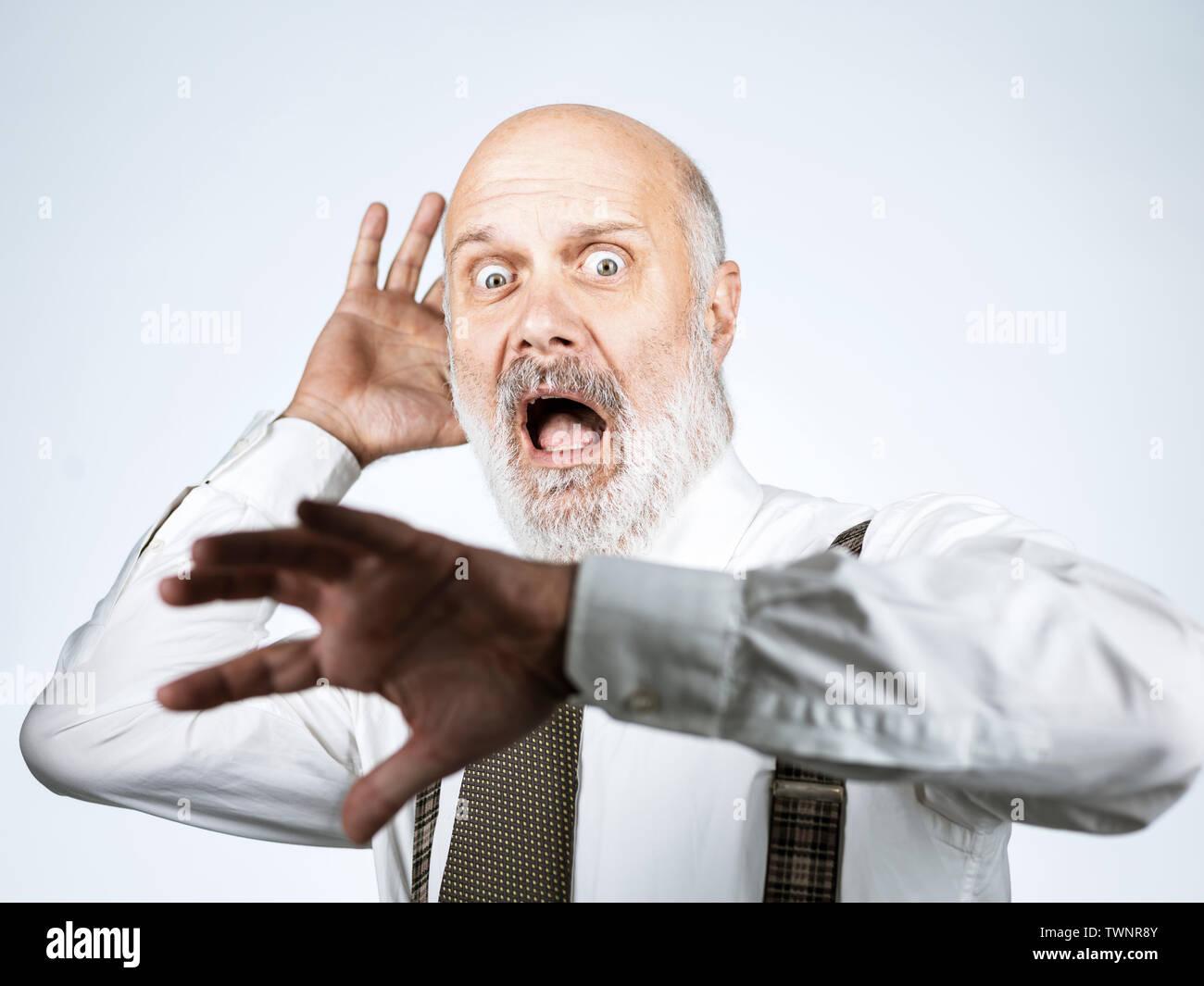 Angst Panik älterer Mann laut schreiend mit erhobenen Händen Stockbild