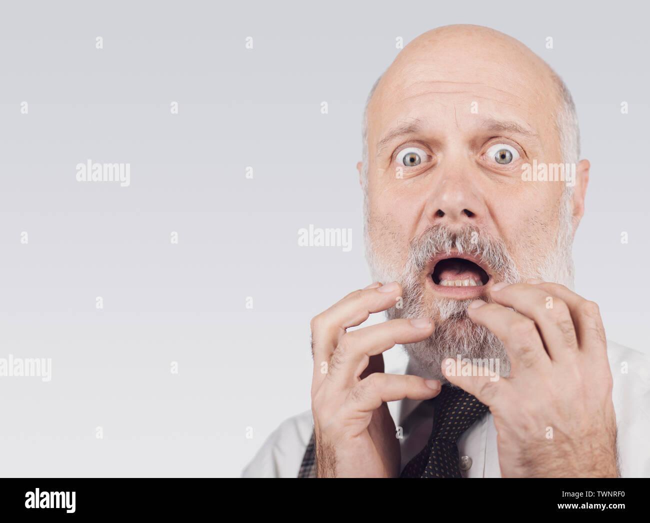 Älterer Mann keuchte und Kamera erschreckt, ist er geschockt und hoffnungslos Stockbild