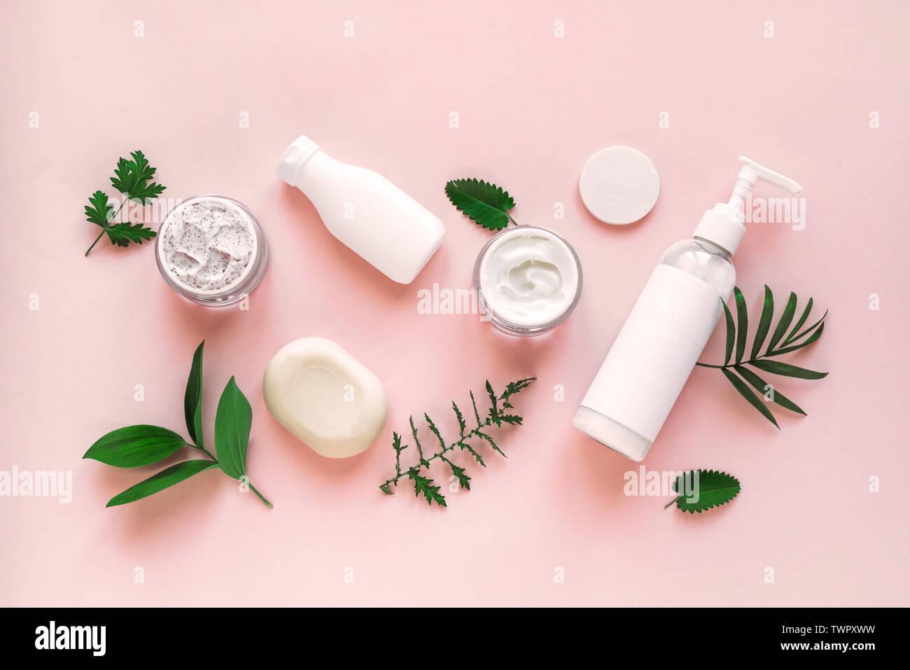 Naturkosmetik und grüne Blätter auf rosa Hintergrund, Ansicht von oben, flach. Natürliche organische Hautpflege, Bio Forschung und gesunden Lebensstil Konzept. Stockfoto