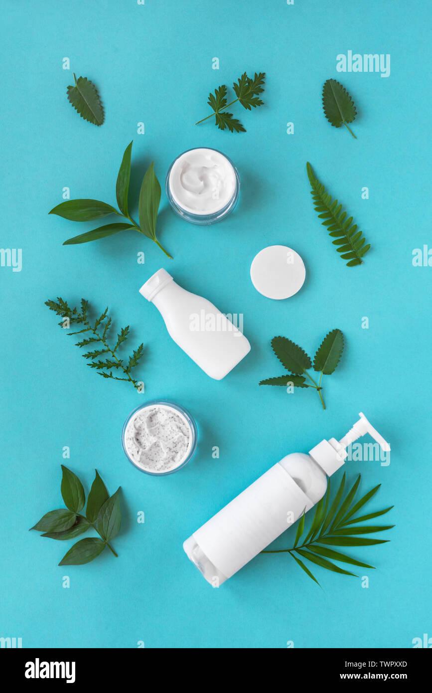 Naturkosmetik und grüne Blätter auf blauem Hintergrund, Ansicht von oben, flach. Natürliche organische Hautpflege, Bio Forschung und gesunden Lebensstil Konzept. Stockfoto