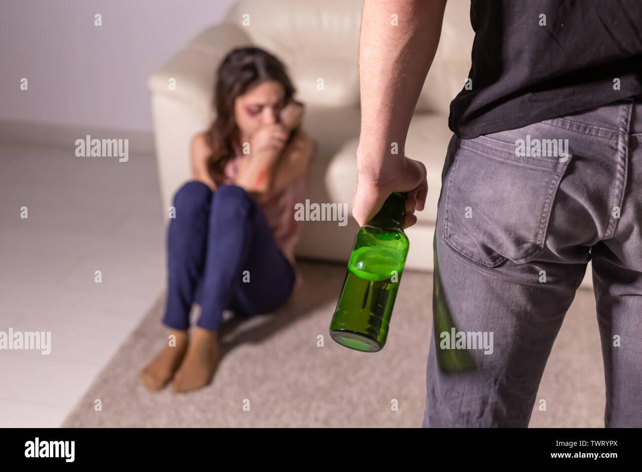 Häusliche Gewalt, Alkohol und Missbrauch Konzept - betrunkener Mann mit Flasche missbraucht seine Frau auf dem Boden liegend Stockbild