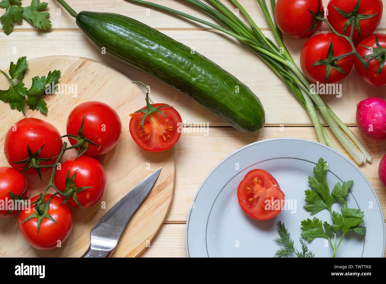 Gesunde Lebensmittel Zutaten zum Kochen auf hölzernen Küchentisch vorbereitet. Frische Tomaten am Zweig, Rettich, Zwiebel, Dill und Petersilie. Mit hellen Holzmöbeln im Landhausstil Stockfoto