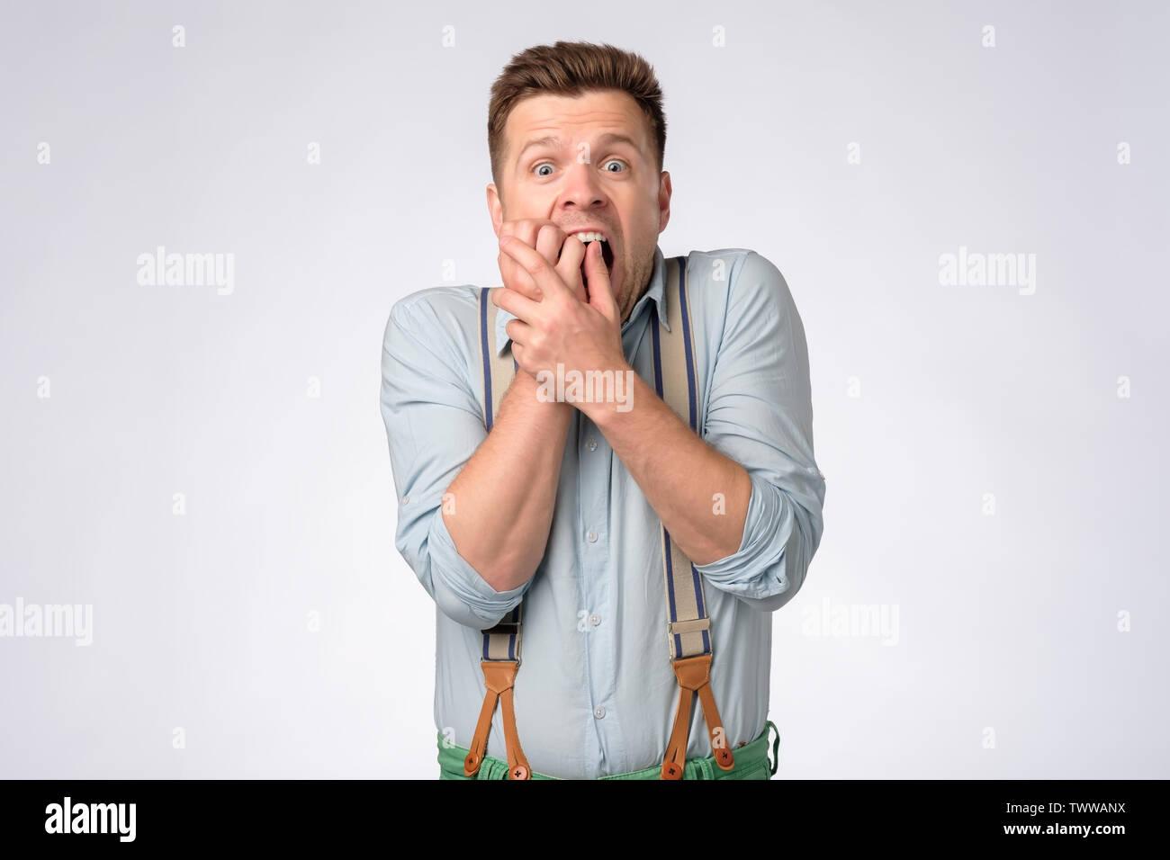 Junger Mann in Hemd und Hosenträgern, Mund mit Händen in Schock Stockbild