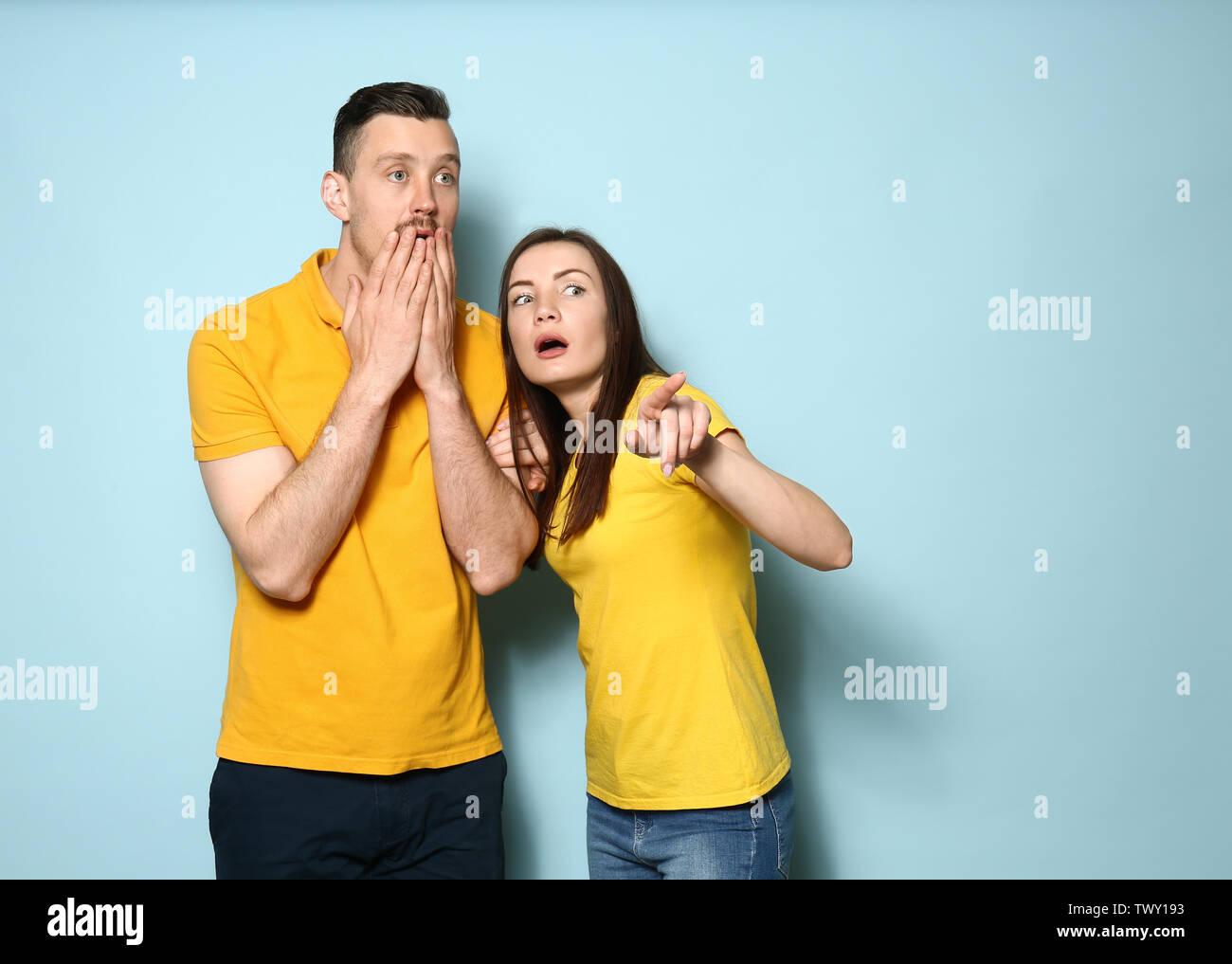 Junges Paar auf Farbe Hintergrund Schockiert Stockbild