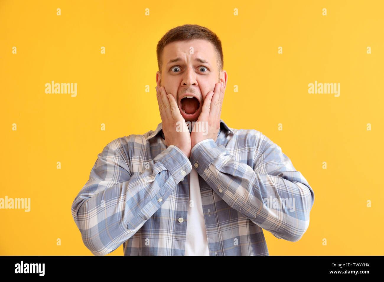 Mann in Panik Attacke auf farbigen Hintergrund Stockbild