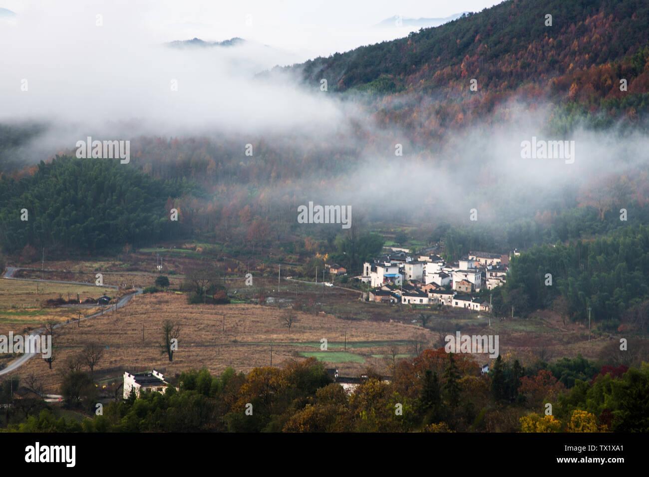 Ein altes Dorf eingehüllt durch Wolken und Nebel. Stockfoto