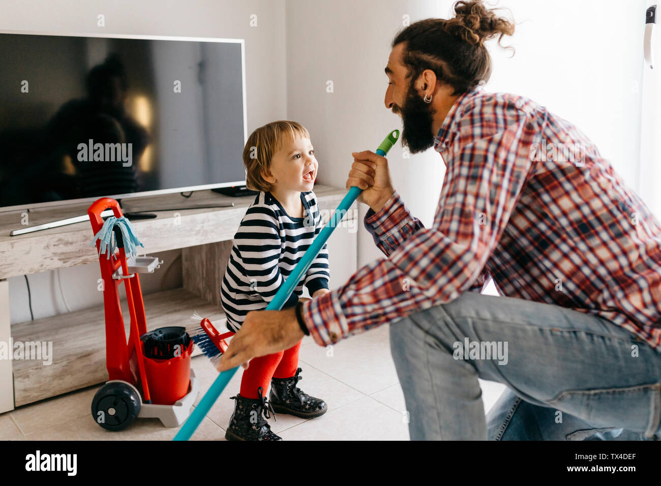 Vater und Tochter Spaß zusammen während der Reinigung der Wohnzimmer Stockfoto