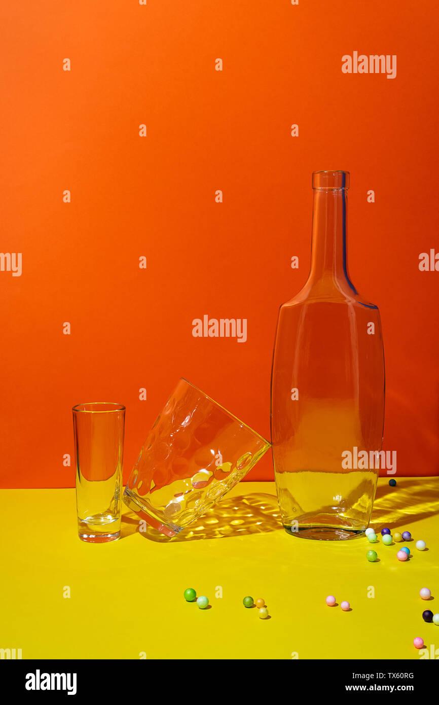 Pop Art noch gestalteten Leben mit leeren Flaschen und Gläser auf Orange und Gelb Stockfoto