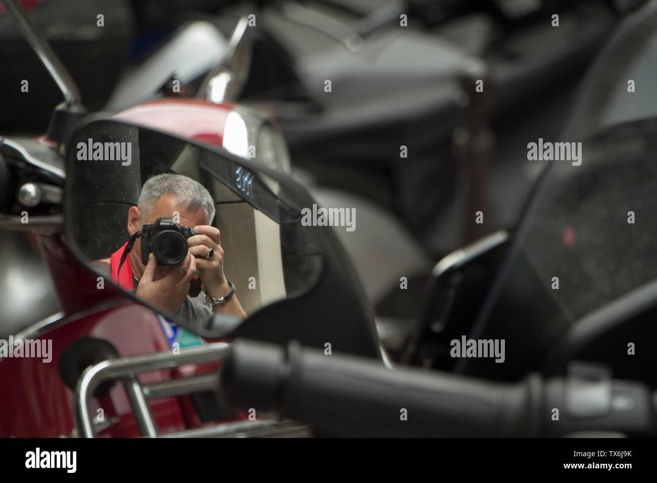 Paris, Frankreich, 05.Juli 2018: Ein Fotograf nimmt seine selfie Im Rückspiegel eines Motorrads geparkt auf einer Straße in Paris. Stockfoto