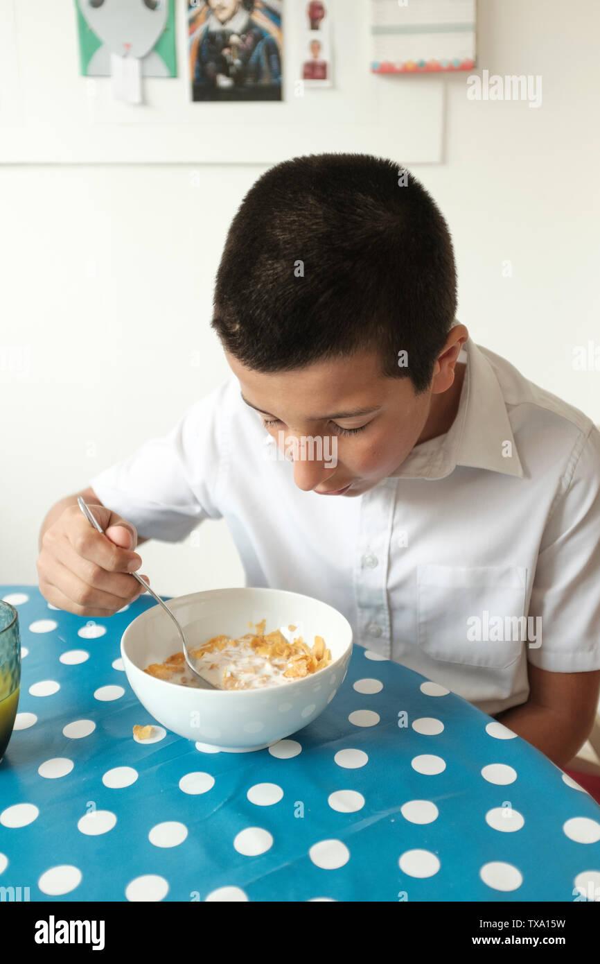 UK, London - Schüler isst Frühstück vor der Schule Stockfoto