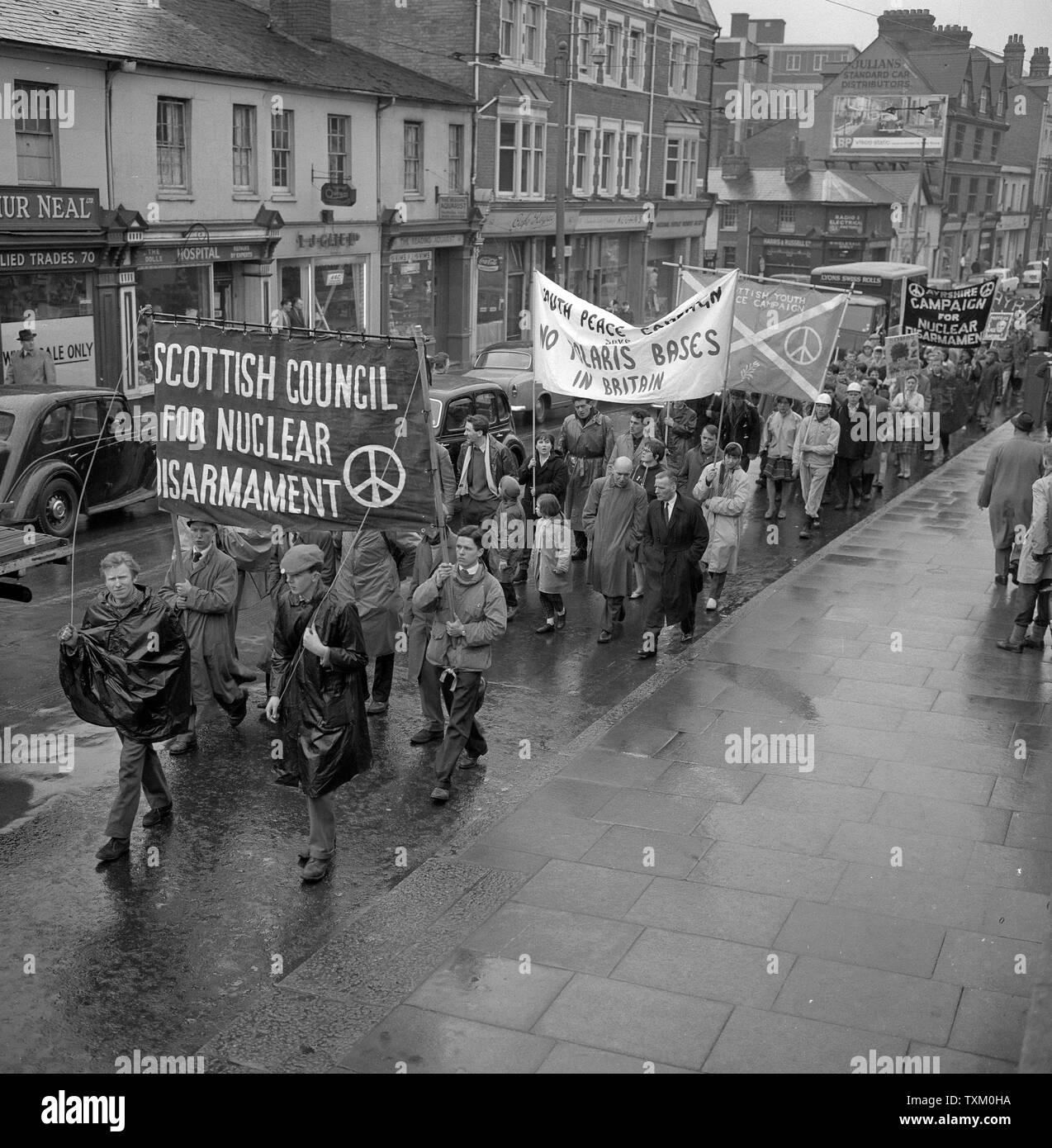 Die Demonstranten tragen mit bunten Bannern, wie sie von der Lesung in der Jährlichen 50 Meile Ban-den-Bombe Marsch vom Atomic Weapons Research Establishment in Aldermaston zum Trafalgar Square, London. Stockfoto