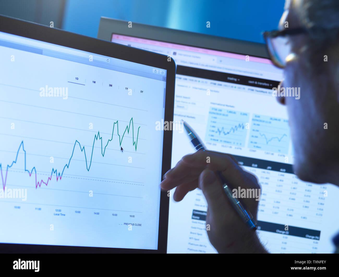 Finanzdienstleistungen, Lager der Analyst untersucht das Aktienkurs Daten eines Unternehmens auf dem Computer Stockfoto